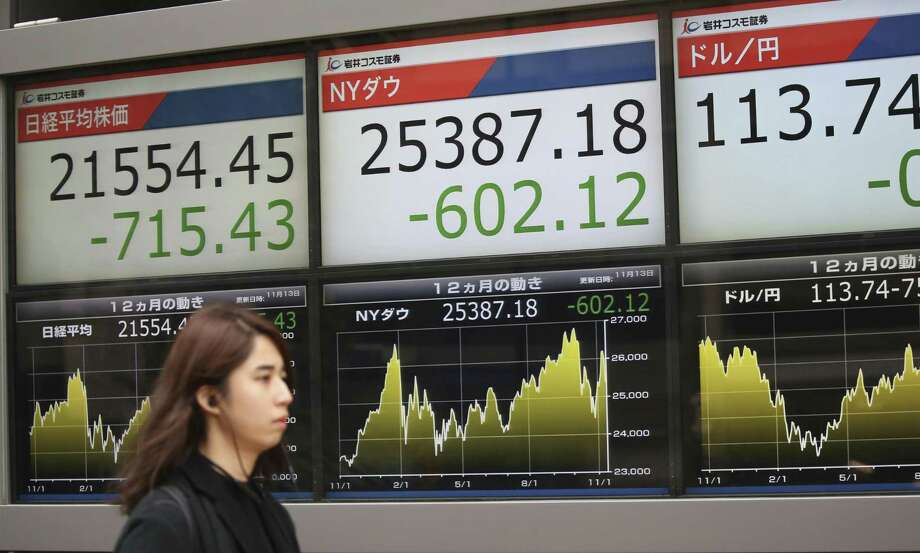 A woman walks by an electronic stock board of a securities firm in Tokyo, Tuesday, Nov. 13, 2018. Asian stocks sank Tuesday after a tech sell-off dragged Wall Street lower. Tokyo's Nikkei 225 tumbled 3.2 percent to 21,554.45. (AP Photo/Koji Sasahara) Photo: Koji Sasahara, STF / Associated Press / Copyright 2018 The Associated Press. All rights reserved.