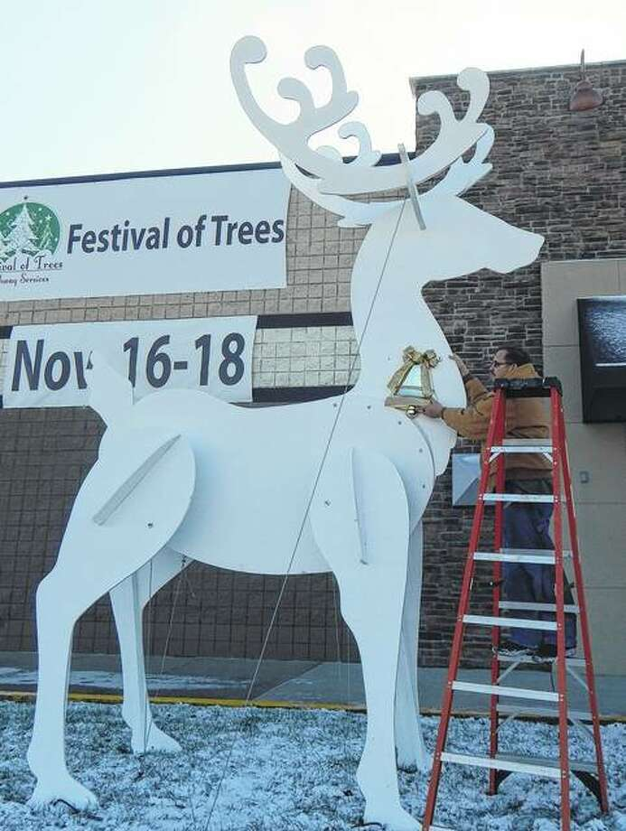 Steve Seymour works Tuesday to put the finishing touches on one of two giant wood reindeer he built to welcome visitors to the Festival of Trees at Pathway Services on Morton Avenue. The festival begins at 5 p.m. Friday and runs through the weekend. Photo: Angela Bauer | Journal-Courier