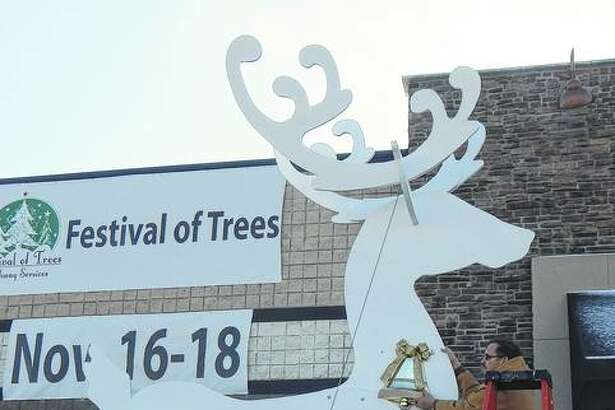Steve Seymour works Tuesday to put the finishing touches on one of two giant wood reindeer he built to welcome visitors to the Festival of Trees at Pathway Services on Morton Avenue. The festival begins at 5 p.m. Friday and runs through the weekend.