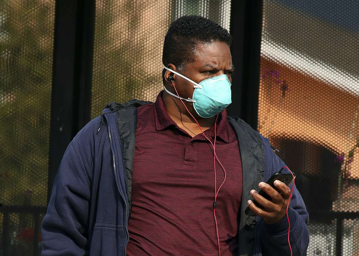 A man wears a mask while waiting for public transit on Wednesday, Nov. 14, 2018, in Alameda, Calif. Authorities have again issued an unhealthy air quality alert for parts of the San Francisco Bay Area as smoke from a massive wildfire drifts south, polluting the air. (AP Photo/Ben Margot)