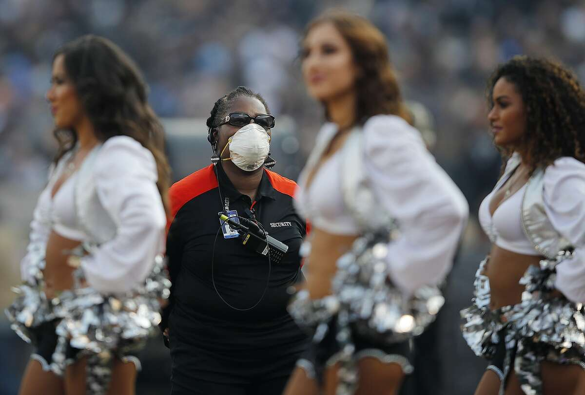 A security guard wears a mask on the field due to wildfires during the second half of an NFL football game between the Oakland Raiders and the Los Angeles Chargers in Oakland, Calif., Sunday, Nov. 11, 2018. (AP Photo/John Hefti)