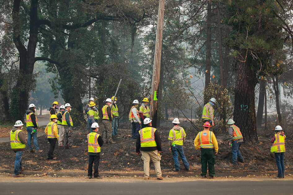 PG&E watch as trees are marked for cutting after the Camp Fire tore through the town of Paradise, California, on Wednesday, Nov. 14, 2018.