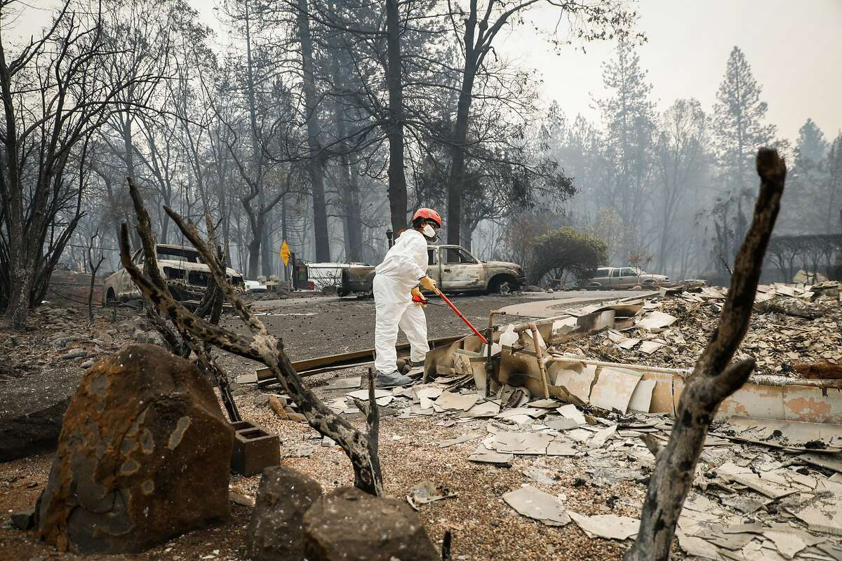 A search and rescue team member surveys a property for remains following the Camp Fire in Paradise, California, on Wednesday, Nov. 14, 2018.