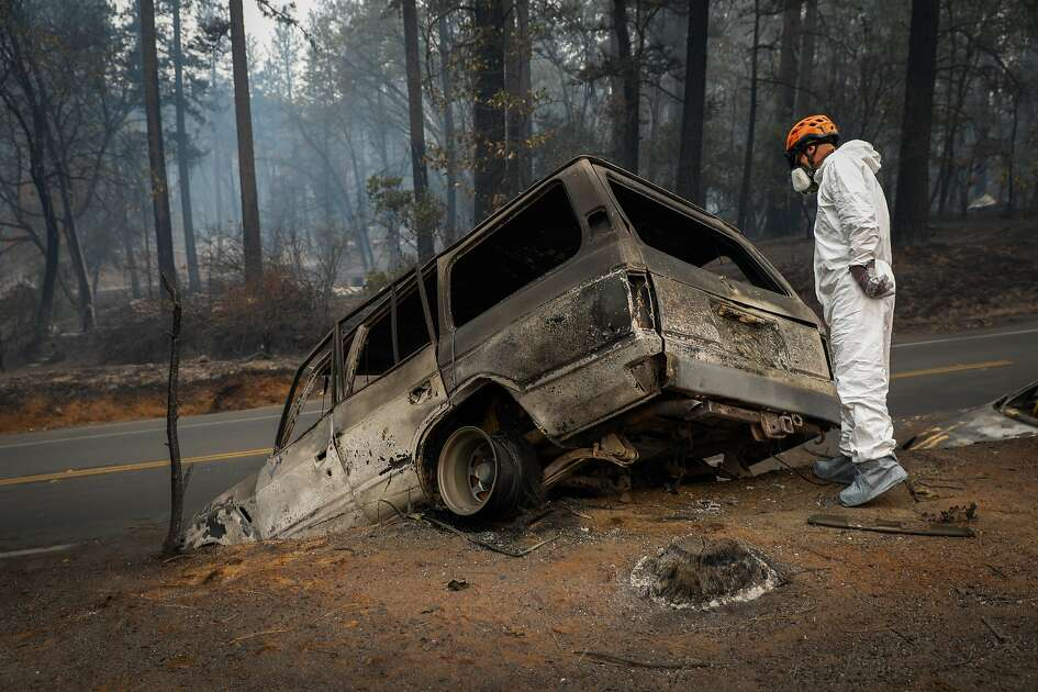 A man with a search and rescue team surveys a car for remains following the Camp Fire in Paradise, California, on Wednesday, Nov. 14, 2018.