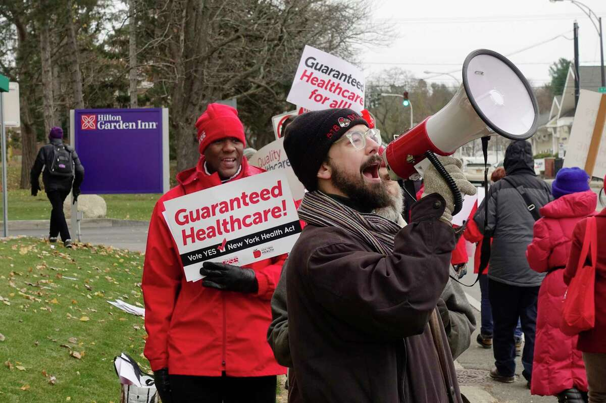 Members of unions, activist groups and healthcare professionals take part in a protest calling for single-payer healthcare outside the Hilton Garden Inn on Thursday, Nov. 15, 2018, in Troy, N.Y. The annual New York Health Plan Association was holding a conference at the hotel. Those protesting say that the New York Health Plan Association is lobbying against the New York Health Act, which would create a single-payer healthcare system in the state. (Paul Buckowski/Times Union)