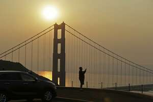 Mahmoud El Tahawy, of Egypt, looks out at the smoke from wildfires obscuring the San Francisco skyline behind the Golden Gate Bridge Friday, Nov. 9, 2018, near Sausalito, Calif. A California fire official says a blaze in Northern California nearly quadrupled in size overnight. Capt. Scott McLean of the California Department of Forestry and Fire Protection says the fire near the town of Paradise has grown to nearly 110 square miles (285 square kilometers). (AP Photo/Eric Risberg)