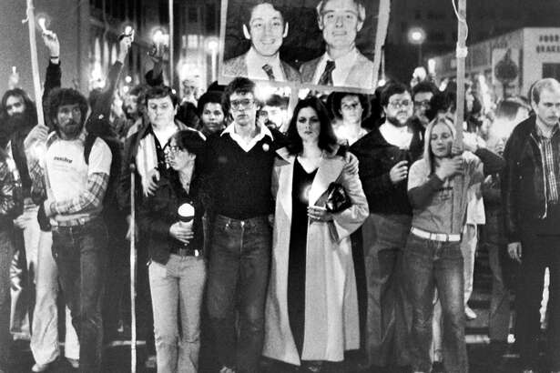 A crowd of 12,000 carried flickering candles as they marched from Castro Street to City Hall to honor slain Mayor George Moscone and Supervisor Harvey Milk, (shown in portrait), on Nov. 27, 1979 on hje first anniversary of their deaths. In foreground is Moscone's daughter, Jennifer, 22, (light coat), as she leads the parade with Cleve Jones, Harvey Milk's former assistant.