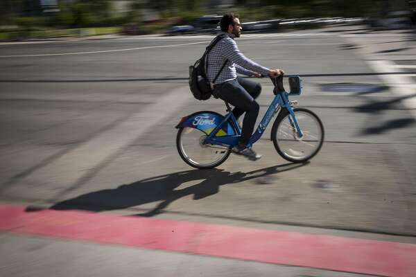 A cyclist rides a Ford GoBike in San Francisco, California, U.S., on Monday, June 11, 2018. Lyft Inc. is in discussions to acquire Ford GoBike and Citi Bike operator Motivate for $250 million, a person familiar with the matter said. The acquisition, if it goes through, would thrust the second-largest U.S. ride-hailing company into the middle of the brewing war over electric scooters and bikes that's beginning to roil American cities. Photographer: David Paul Morris/Bloomberg