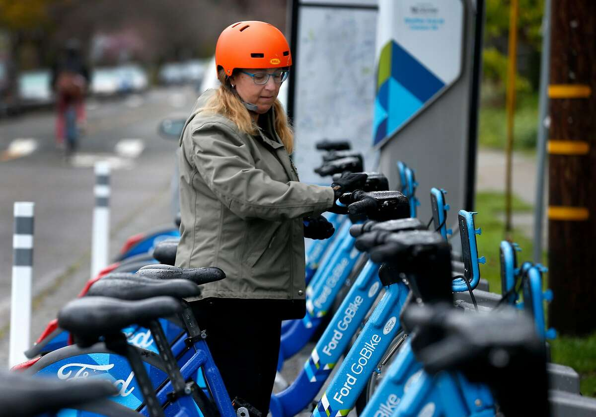 Wendy Wheeler undocks a Ford GoBike in the Rockridge neighborhood for her three-mile commute by bicycle in Oakland, Calif. on Thursday, March 8, 2018. A few weeks back, Wheeler narrowly avoided an accident after discovering a vandal had cut the brake line on one of the shared bikes she was riding.