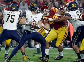 Cal quarterback Chase Garbers hold the ball in the pocket under pressure from USC defensive lineman Liam Jimmons in the second quarter on Saturday, Nov. 10, 2018, at the Los Angeles Memorial Coliseum. (Luis Sinco/Los Angeles Times/TNS)
