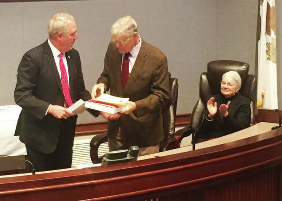 At a ceremony at the Madison County Administration building last month, U.S. Rep. John Shimkus, R-Collinsville, at left, presents retiring state Sen. William Haine, D-Alton, with a flag flown over the U.S. Capital for his retirement. Haine was honored this week with a retirement resolution in the Illinois State Senate. Photo: For The Telegraph