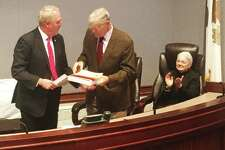 At a ceremony at the Madison County Administration building last month, U.S. Rep. John Shimkus, R-Collinsville, at left, presents retiring state Sen. William Haine, D-Alton, with a flag flown over the U.S. Capital for his retirement. Haine was honored this week with a retirement resolution in the Illinois State Senate.