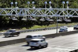 Cars pass under toll sensor gantries hanging over the Massachusetts Turnpike. A new study says that Connecticut could make a billion dollars a year in revenue if it introduced electronic highway tolls.