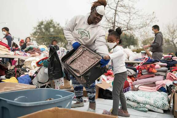 A woman who was displaced and wished not to be named and her daughter unzip a suitcase to take while sifting through a donation site at a temporary encampment in the parking lot of Walmart in  Chico, Calif. Wednesday, Nov. 14, 2018 for those who lost their homes or have been displaced by the Camp Fire.