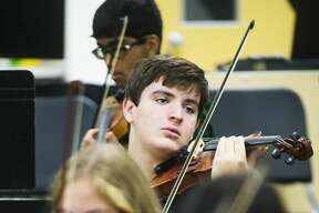 Dow High students tune their instruments during orchestra class on Thursday, Nov. 15, 2018. Orchestra students, along with choirs, bands, pom squads and more will be performing during the school's annual variety show, RenFair, at 7 p.m. Saturday, Nov. 17 at Midland Center for the Arts. (Katy Kildee/kkildee@mdn.net)