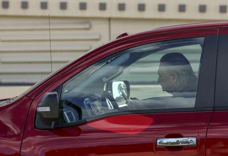 A motorist uses a cell phone while driving on the 610 West Loop in Houston.
