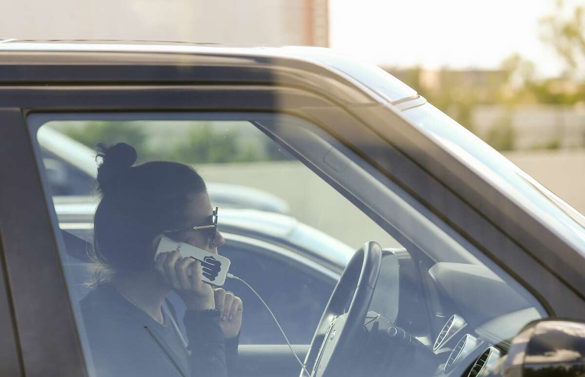 A motorist uses a cell phone while driving in traffic.