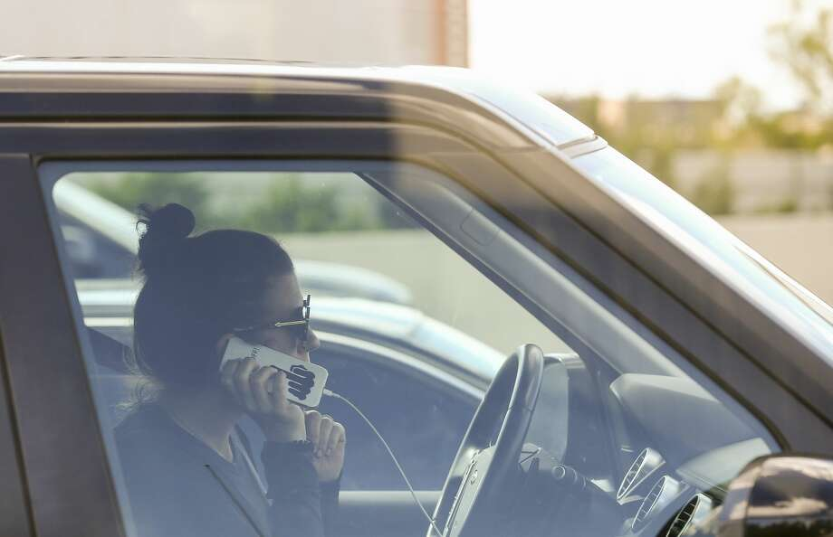 A motorist uses a cell phone while driving in traffic. Photo: Godofredo A. Vasquez/Staff Photographer