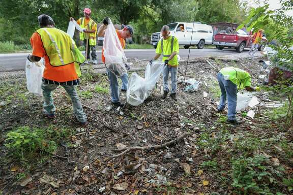 On Our Own Services workers and field leads pick up trash along Corder Street near Scott Street Tuesday, Oct. 9, 2018, in Houston.