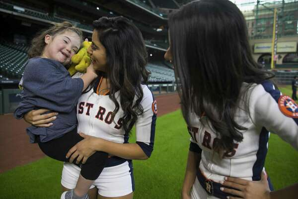 Six-year-old Lily Skeen smiles with Shooting Stars Sara Gonzalez and Nahomi Gonzalez during the annual Sunshine Kids Party at Minute Maid Park. Participants went up to bat against Biggio, ran the bases, explored the field, enjoyed lunch and received lots of Astros goodies.