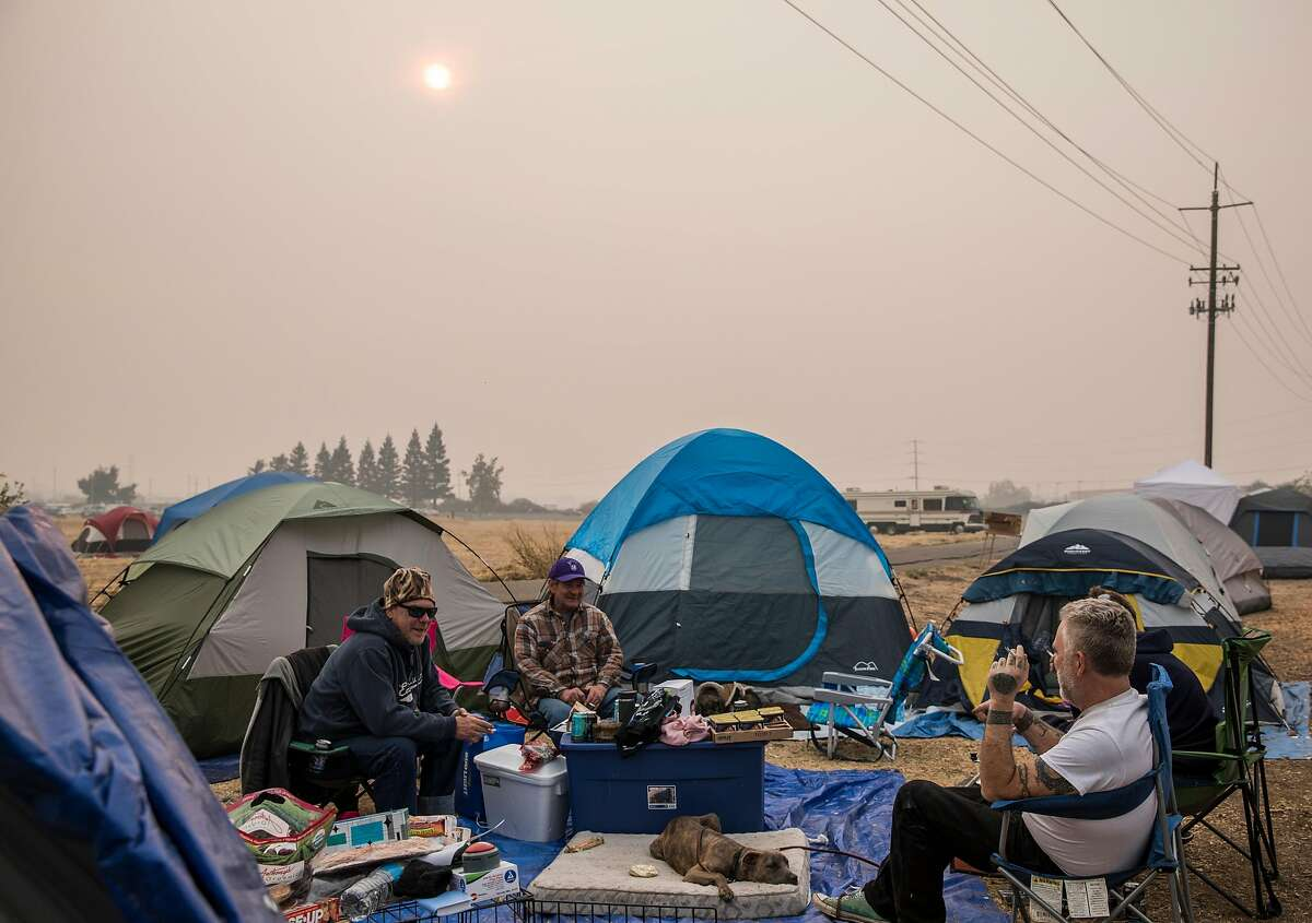 A group of friends who lost their home in Paradise, roll cigarettes while at a temporary encampment in the parking lot of Walmart in Chico, Calif. Wednesday, Nov. 14, 2018 for those who lost their homes or have been displaced by the Camp Fire.