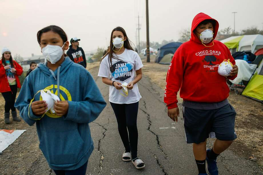 (l-r) Marcella Solis, 12, Alicia Pineda,12 and Efren Solis, 12, of Chico, walk through a makeshift evacuation center at Walmart in Chico handing out masks to people who need them following the Camp Fire that tore through Paradise last week in Chico, California, on Wednesday, Nov. 14, 2018. Photo: Gabrielle Lurie / The Chronicle
