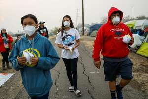 (l-r) Marcella Solis, 12, Alicia Pineda,12 and Efren Solis, 12, of Chico, walk through a makeshift evacuation center at Walmart in Chico handing out masks to people who need them following the Camp Fire that tore through Paradise last week in Chico, California, on Wednesday, Nov. 14, 2018.