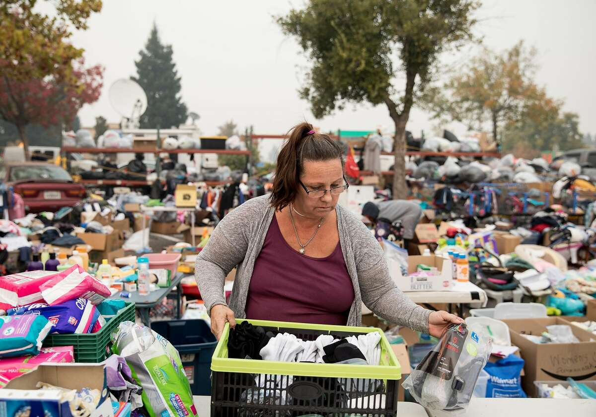 Denise Meyers, a volunteer from Marysville, sorts through toiletries at a donation drop-off site located at a temporary encampment in the parking lot of Walmart in Chico, Calif. Wednesday, Nov. 14, 2018 for those who lost their homes or have been displaced by the Camp Fire.