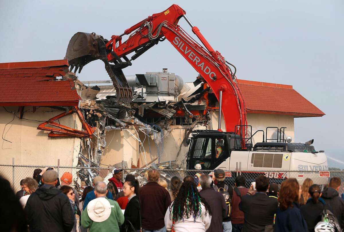 Curious onlookers gather to watch a former Burger King and observation post being demolished at the Presidio to make way for the Tunnel Tops redevelopment and landscaping project in San Francisco, Calif. on Thursday, Nov. 15, 2018.