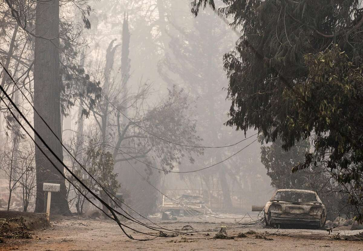 Charred cars and downed power lines are seen on a residential street after the Camp Fire devastated the entire town of Paradise, Calif. Saturday, Nov. 10, 2018.
