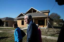 Federal Reserve Chairman Jerome Powell, center, walks a Houston Habitat for Humanity build site during a visit to the Fifth Ward, Thursday, Nov. 15, 2018, in Houston.