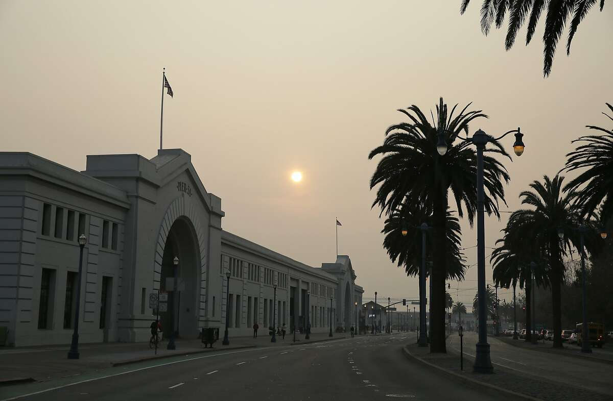 A smoky haze from wildfires obscures the Embarcadero Thursday, Nov. 15, 2018, in San Francisco. Recurring wildfires are sparking concern among medical experts about potentially major health consequences. Dozens of schools across the Bay Area have canceled classes due to the smoke. (AP Photo/Eric Risberg)