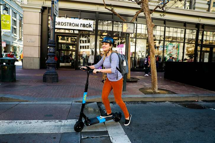 A woman rides a Skip scooter on Market and 5th Streets in San Francisco, California, on Monday, Oct. 15, 2018.