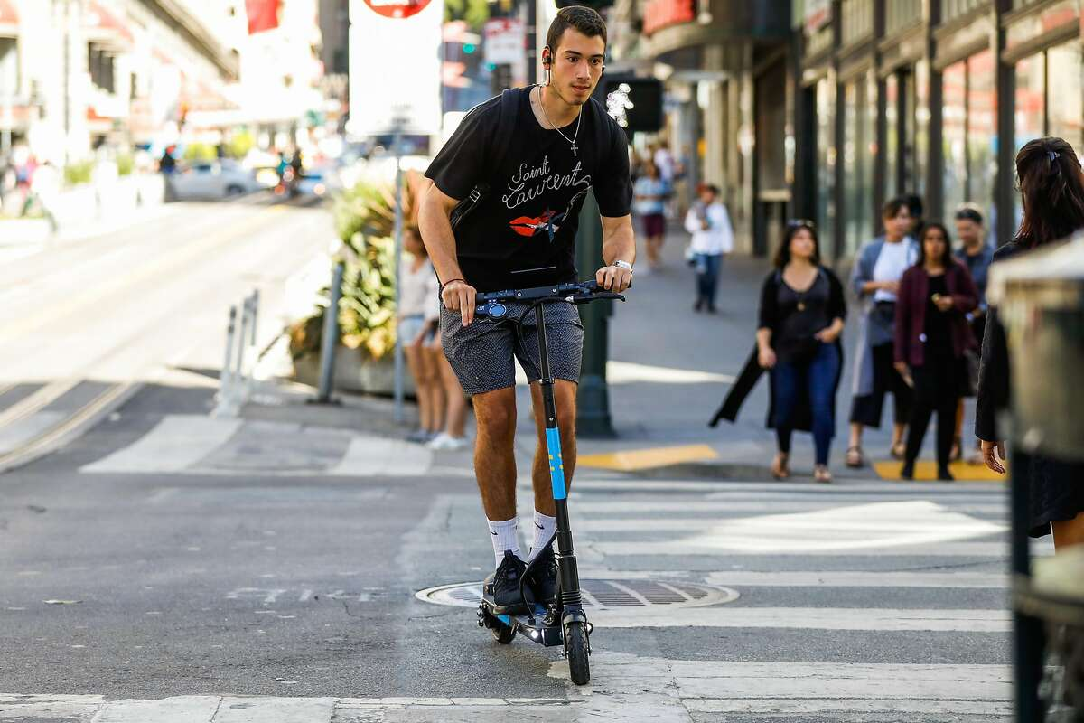 A man rides a Skip scooter on Powell Street in San Francisco, California, on Monday, Oct. 15, 2018.