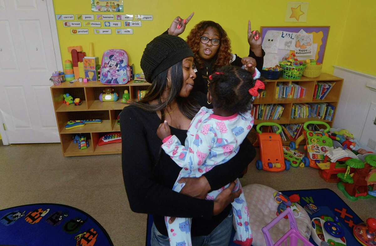 Malta House House Manager Shavon Wright, right, and staffer Brianna Gibbs entertain a child client at Malta House Thursday, November 15, 2018, in Norwalk, Conn.