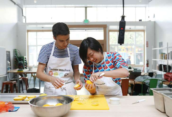 Foud Matin (l to r) and Ashley Qian, Tinker Kitchen members, scoop out oranges while creating a orange creamsicle dish at Tinker Kitchen on Thursday, November 14, 2018 in San Francisco, Calif.
