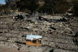 A before photo is placed on the remains of a building leveled in the Woolsey Fire at decimated Paramount Ranch during U.S. Secretary of the Interior Ryan Zinke's visit to the ranch Thursday, Nov. 15, 2018, in Agoura Hills, Calif.