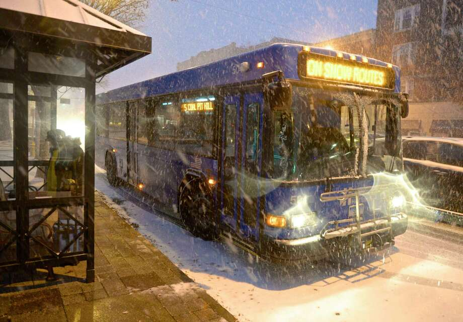 A HART bus drops off a rider on Main Street during the first snow fall of the season.  Photo: H John Voorhees III, Hearst Connecticut Media / The News-Times