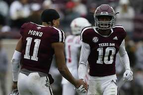 Myles Jones (10)of the Texas A&M Aggies receives a handshake from Kellen Mond (11) after he was ejected from the game for targeting in the fourth quarter against the Mississippi Rebels at Kyle Field on November 10, 2018 in College Station, Texas.