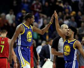 Kevin Durant (35) high fives Quinn Cook (4) in the second half as the Golden State Warriors played the Atlanta Hawks at Oracle Arena in Oakland, Calif., on Tuesday, November 13, 2018.