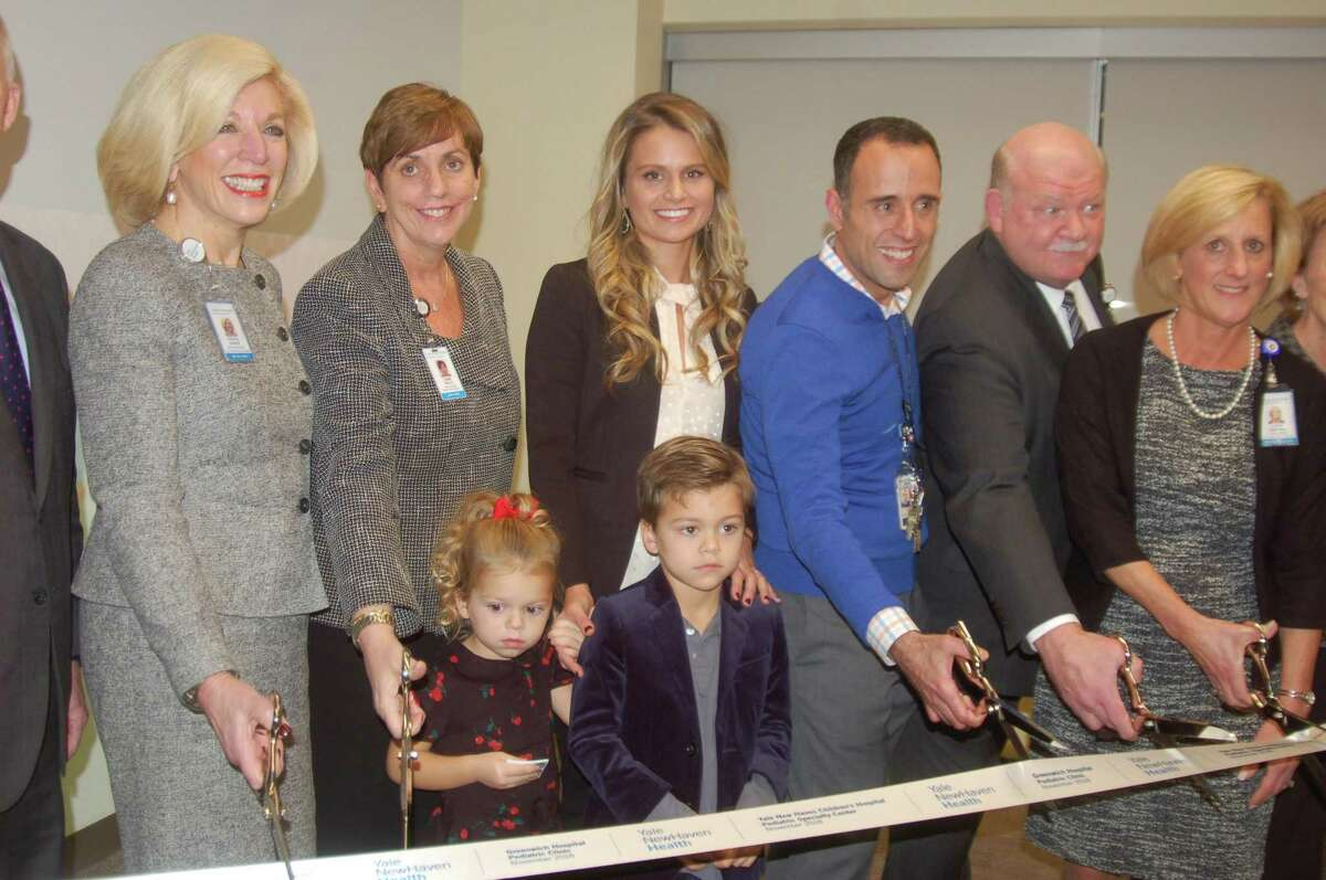From left, Cynthia Sparer from Yale New Haven Hospital; Diane Kelly from Greenwich Hospital; Greenwich resident Kristin Updike with her children Haper and Grayson; Anthony Porter from Yale New Haven Children's Hospital; Norman Roth, Greenwich Hospital's president and CEO; and Lynn Sherman from Yale New Haven all take part in the ribbon-cutting Wednesday night for the new center on West Putnam Avenue. It will offer pediatric care as part of the Yale New Haven/Greenwich Hospital partnership.
