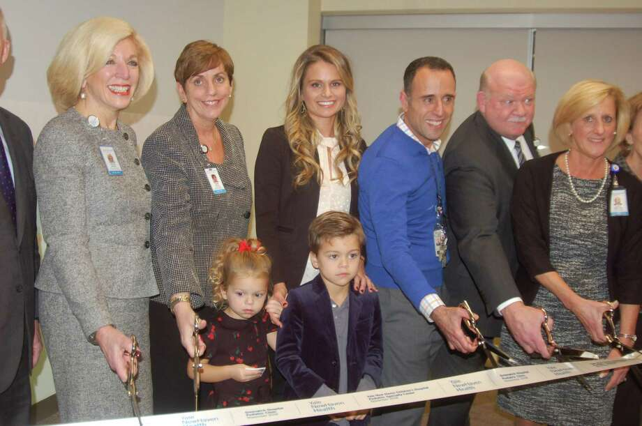 From left, Cynthia Sparer from Yale New Haven Hospital; Diane Kelly from Greenwich Hospital; Greenwich resident Kristin Updike with her children Haper and Grayson; Anthony Porter from Yale New Haven Children's Hospital; Norman Roth, Greenwich Hospital's president and CEO; and Lynn Sherman from Yale New Haven all take part in the ribbon-cutting Wednesday night for the new center on West Putnam Avenue. It will offer pediatric care as part of the Yale New Haven/Greenwich Hospital partnership. Photo: Ken Borsuk / Hearst Connecticut Media /