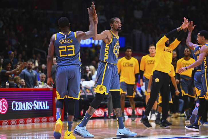Golden State Warriors Forward Draymond Green (23) gives Golden State Warriors Forward Kevin Durant (35) a high five during a NBA game between the Golden State Warriors and the Los Angeles Clippers on November 12, 2018 at STAPLES Center in Los Angeles, CA.