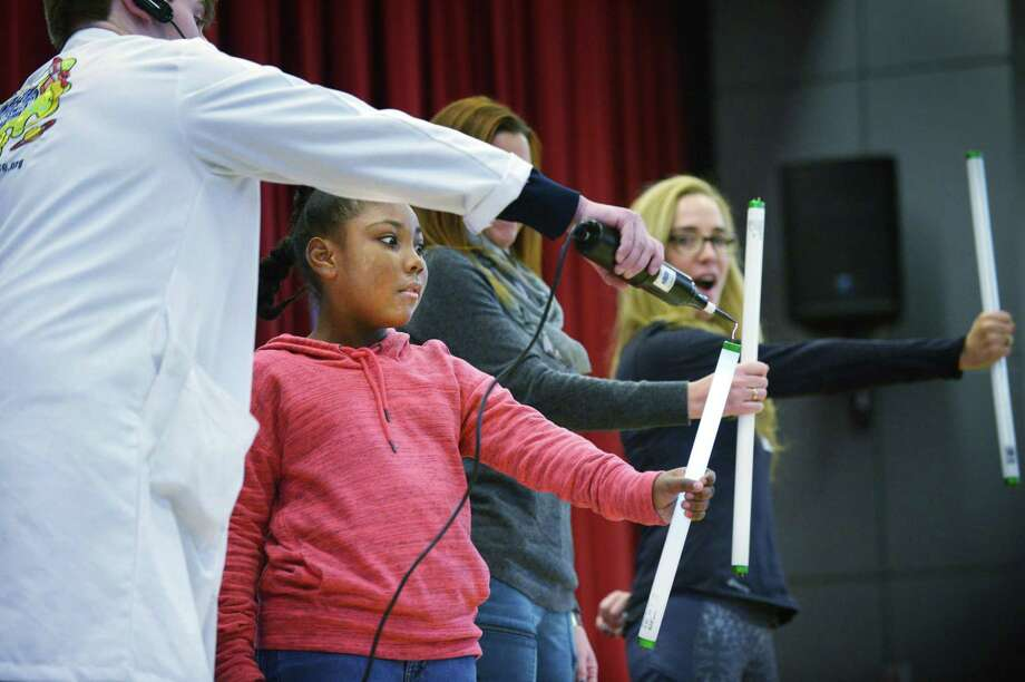 """Mad Science's """"Radical"""" Ryan Borchardt demonstrates conductivity for third grader Jayea Eason and parents Andrea Gottlieb and Sarah Wayland in a program designed to teach students how to reduce, reuse and recycle at Rowayton Elementary School Thursday, November 15, 2018, in Norwalk, Conn. Students also learned about composting and saving water and how to become a more energy-efficient society. Photo: Erik Trautmann / Hearst Connecticut Media / Norwalk Hour"""