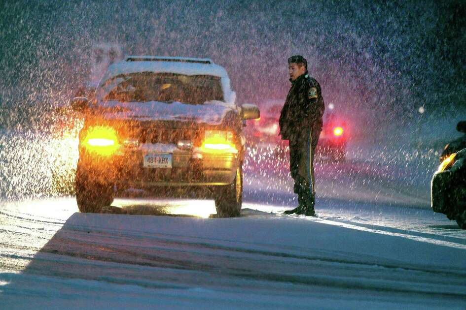 As heavy snow falls, a Trumbull police officer investigates a minor accident at the entrance to the Merritt Parkway at Park Ave in Trumbull, Conn., on Thursday, Nov. 15, 2018. The snow which started falling in the later afternoon, caused many cars to be stuck along Park Ave and other roads around the area.