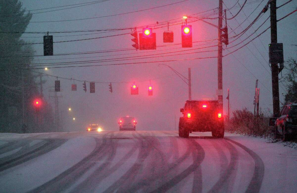 As heavy snow falls, traffic waits for the lights to change at Park Ave in Trumbull, Conn., on Thursday, Nov. 15, 2018. The snow which started falling in the later afternoon, caused many cars to be stuck along Park Ave and other roads around the area.
