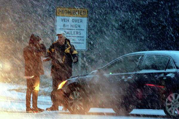 As heavy snow falls, two drivers talk after a minor accident at the entrance to the Merritt Parkway at Park Ave in Trumbull, Conn., on Thursday, Nov. 15, 2018. The snow which started falling in the later afternoon, caused many cars to be stuck along Park Ave and other roads around the area.