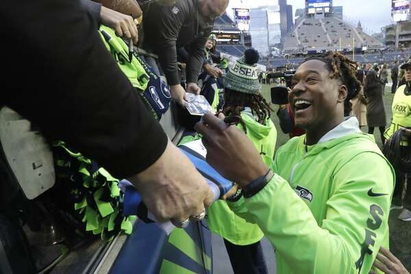 Seattle Seahawks cornerback Shaquill Griffin signs autographs for fans before an NFL football game against the Green Bay Packers, Thursday, Nov. 15, 2018, in Seattle. (AP Photo/Elaine Thompson)