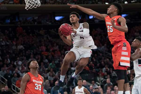 Connecticut guard Jalen Adams (4) goes to the basket against Syracuse guard Tyus Battle (25) during the second half of an NCAA college basketball game in the 2K Empire Classic, Thursday, Nov. 15, 2018, at Madison Square Garden in New York. Connecticut won 83-76.
