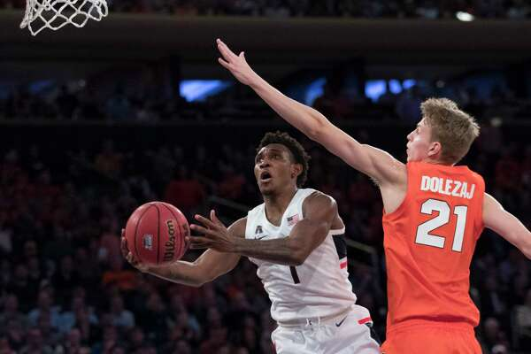 Connecticut guard Christian Vital (1) goes to the basket against Syracuse forward Marek Dolezaj (21) during the second half of an NCAA college basketball game in the 2K Empire Classic, Thursday, Nov. 15, 2018, at Madison Square Garden in New York. Connecticut won 83-76.